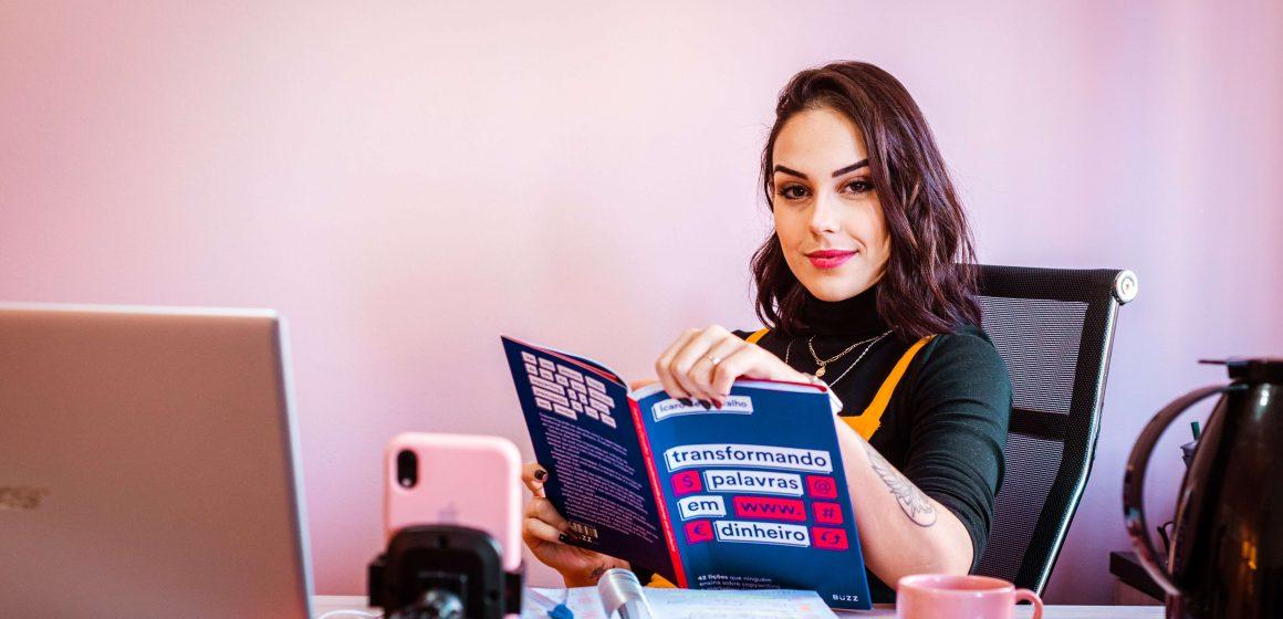Uśmiechnięta kobieta zerka zza książki
