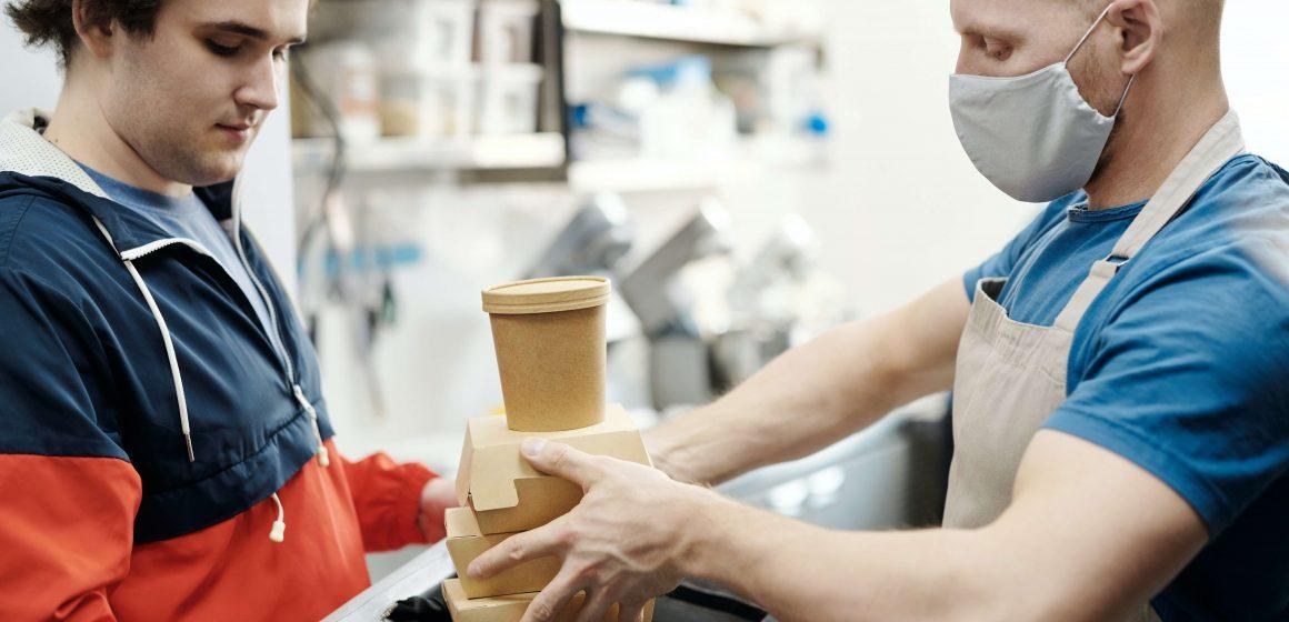 Pracownik restauracji w maseczce przekazuje zamówienie