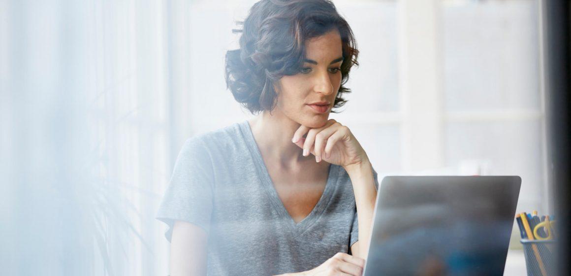Zaciekawiona kobieta przy laptopie